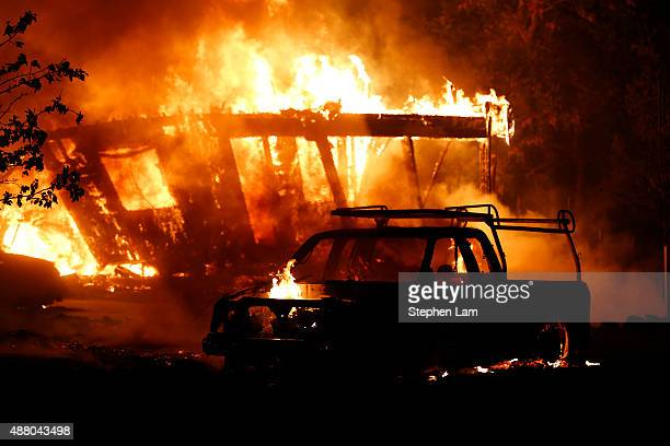 A car burns in front of a burning home during Valley Fire on September 13 2015 in Middletown California The fastmoving fire has consumed 40000 acres...