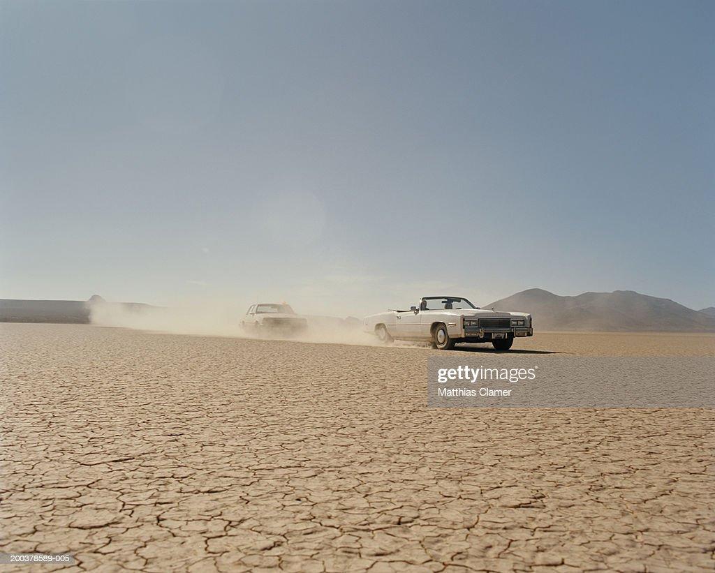 Car chasing convertible in desert : Stock Photo