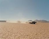 Car chasing convertible in desert