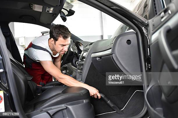 Car cleaning, man hoovering car interior