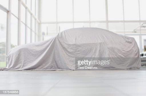 Car covered in cloth in garage