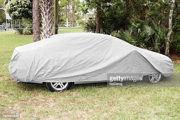 Car covered with textile cover to protect from elements.