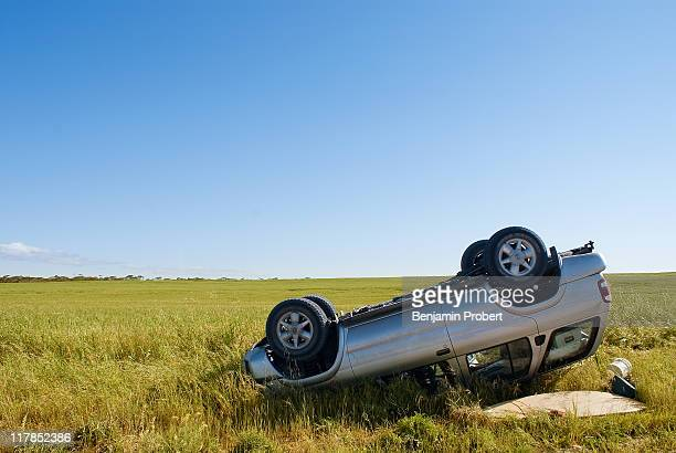 Car crashed on country road with field and sky