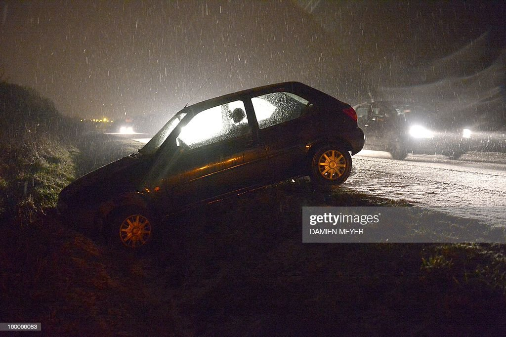 A car crashed on the side of a snow-covered road on January 25, 2013 near Rennes, western France.