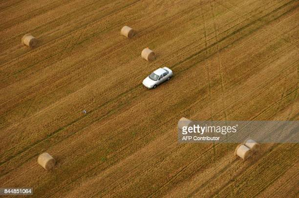 A car crosses bundles of straw in a field in the outskirts of Minsk on September 9 during the Minsk 950th Anniversary Balloon Cup Some 35 crews of...