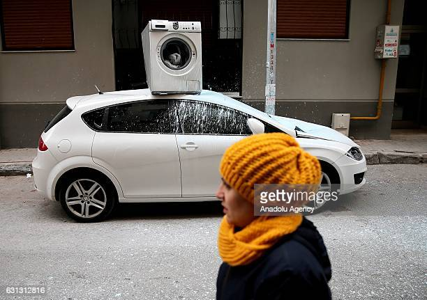 A car damaged after a washing machine thrown out of a third floor apartment balcony is seen in Izmir Turkey on January 9 2017 A washing machine is...