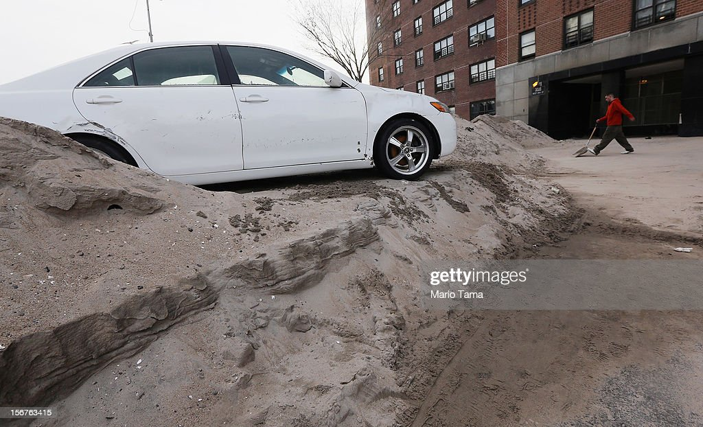 A car damaged and carried by flooding rests atop sand washed in by Superstorm Sandy in the Coney Island neighborhood on November 20, 2012 in the Brooklyn borough of New York City. The Coney Island area was hard hit by Superstorm Sandy.