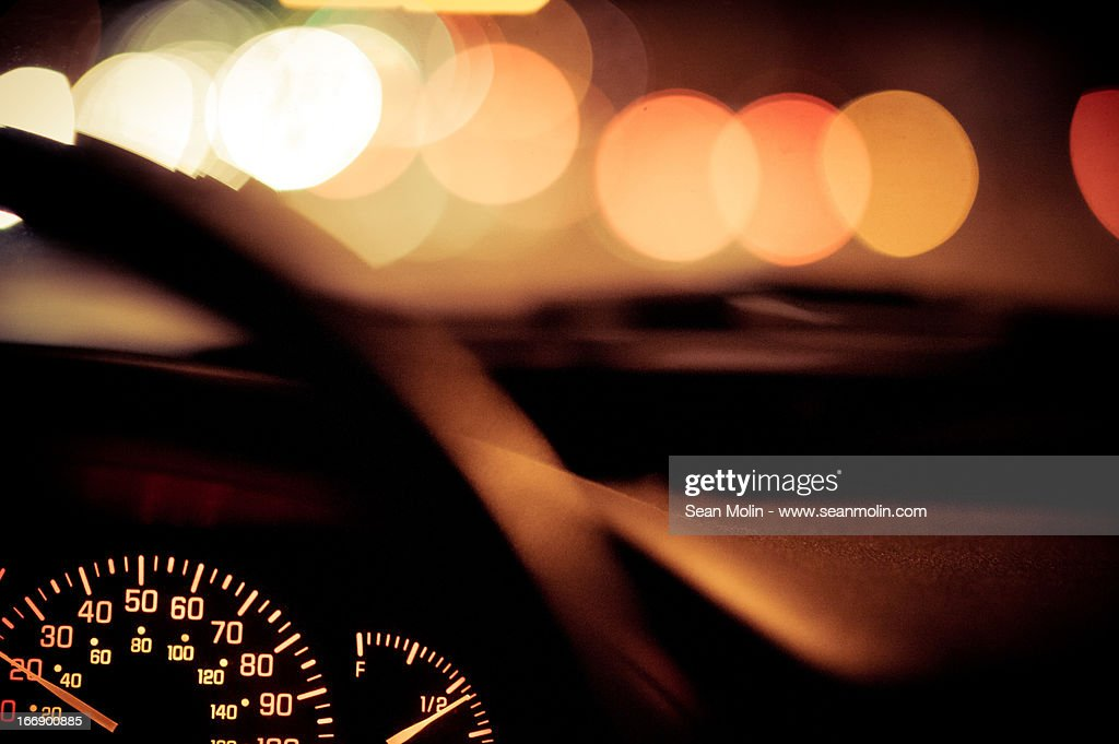 Car dashboard at night with blurred lights : Stock Photo