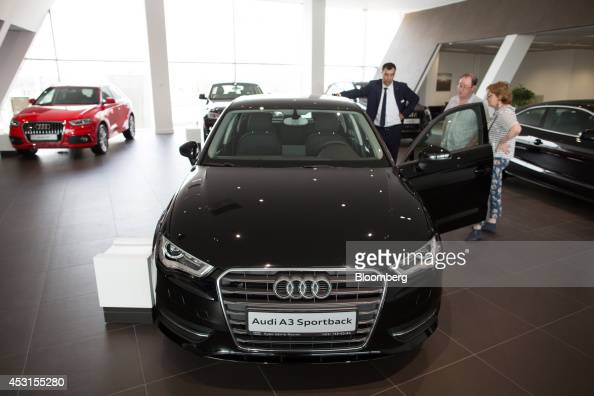 A car dealer assists customers right inspecting an Audi A3 Sportback automobile on display inside an Audi AG showroom in Moscow Russia on Saturday...