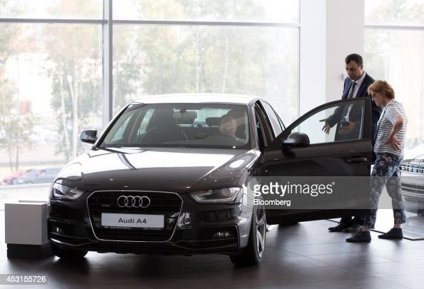 A car dealer assists customers right inspecting an Audi A4 automobile on display inside an Audi AG showroom in Moscow Russia on Saturday Aug 2 2014...
