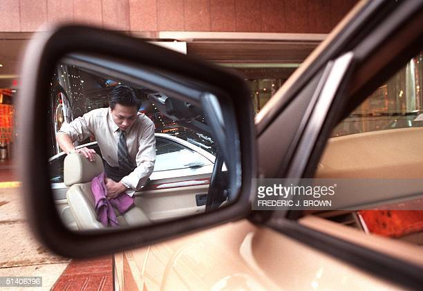 A car dealer cleans the seat of a 1994 BMW 325i at a secondhand car sale in Hong Kong 14 February The asking price for this convertible model is...