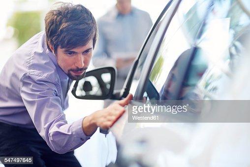Car dealer examining car