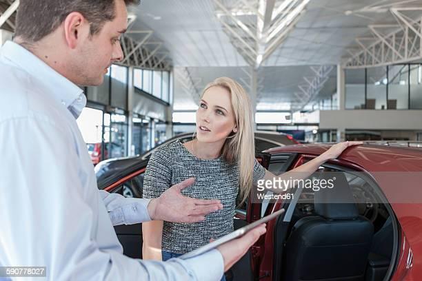 Car dealer explaining new car to young woman