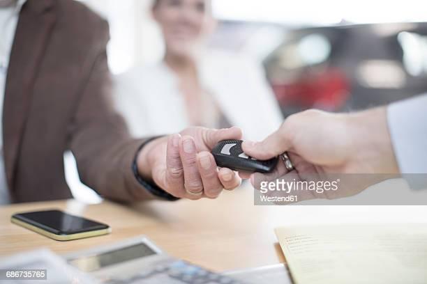 Car dealer handing over key to man at car dealership