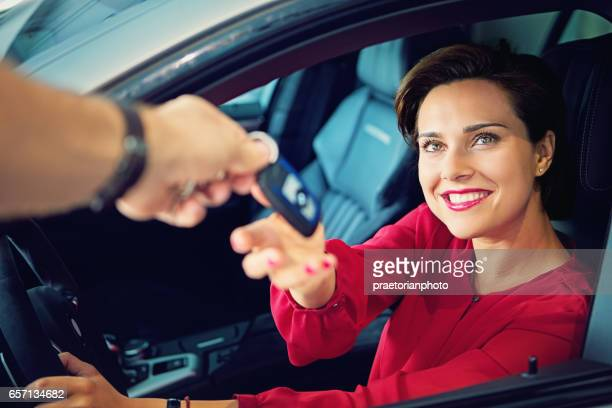 Car dealer is giving car key to a businesswoman
