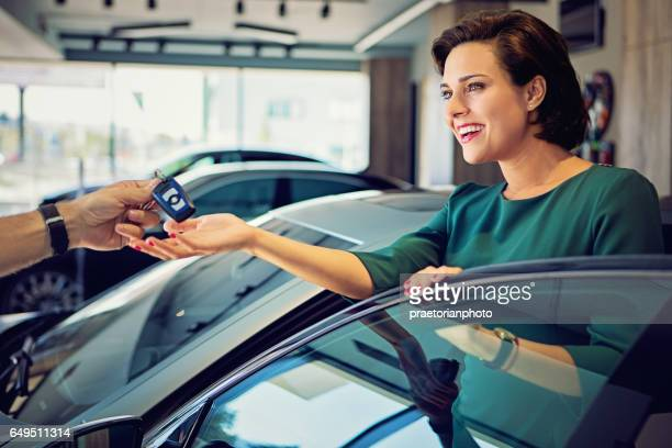 Car dealer is giving car keys to a businesswoman