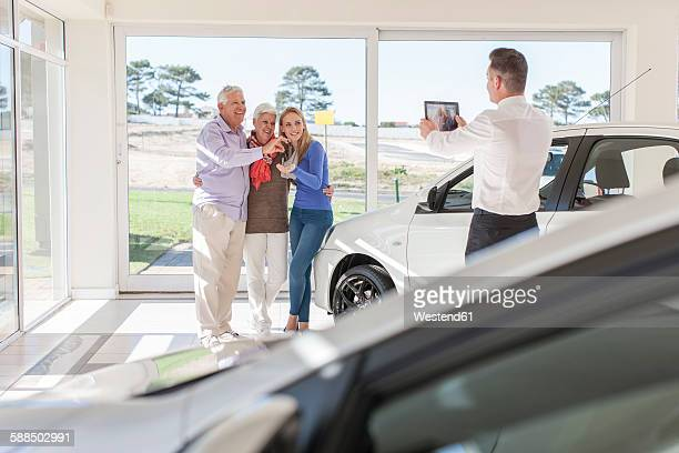 Car dealer taking picture of happy family with car key