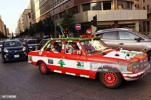 A car decorated in the colors of the Lebanese flag drives down a street at the start of the summer season for the Mediterranean city on June 23 2014...