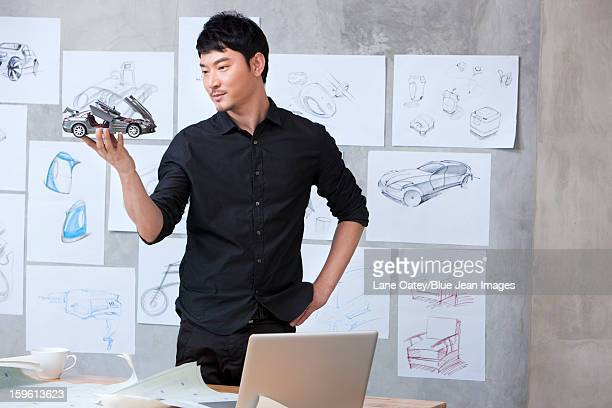 Car designer holding model car in studio