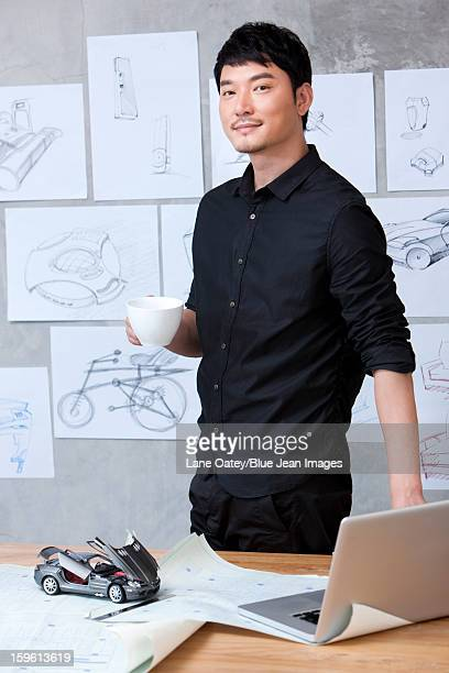 Car designer with a cup of coffee in studio