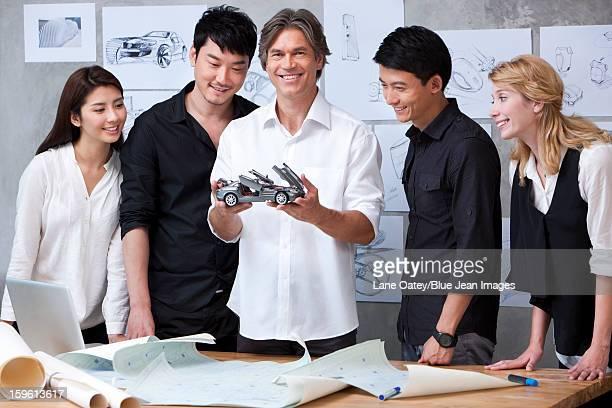 Car designers studying a model car