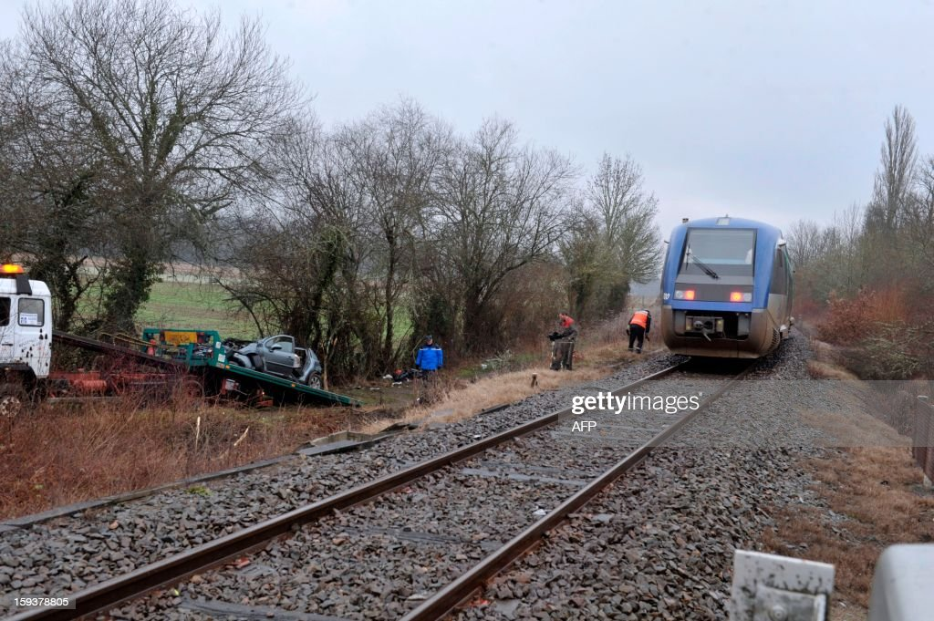 A car destroyed after striking a regional train (TER) in a crossing is lifted by a truck on January 12, 2013 in Sarrazac. Three passengers of the car have been killed in the accident and a fourth was heavily injured.