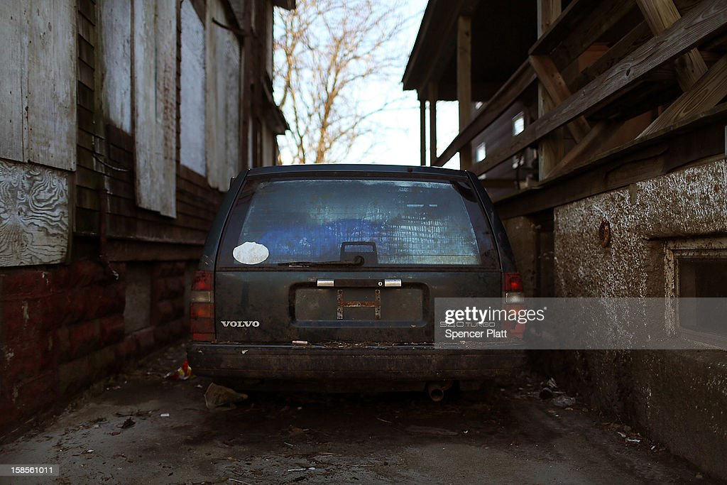 A car destroyed by flood waters sits in the driveway of a damaged home in the Rockaway neighborhood on November 19, 2012 in the Queens borough of New York City. As the holidays approach after Superstorm Sandy slammed into parts of New York and New Jersey, thousands of residents and businesses are still recovering from the devastation.
