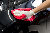 Closeup of hand cleaning black car