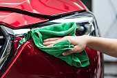Closeup of hand of worker polishing red car