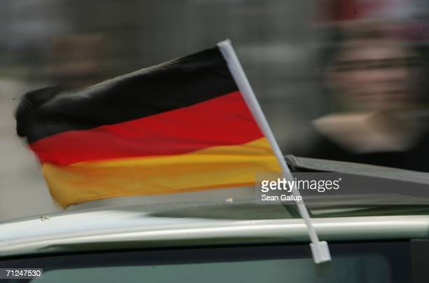 A car displays a German flag as a woman walks by June 19 2006 in Berlin Germany Flags and other soccer images are comon fixtures throughout the...