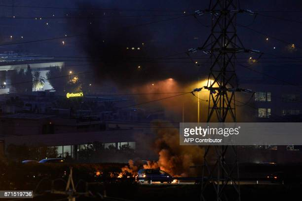 Car drive as a fire burns at a picket on the Ronda de Dalt road in Barcelona during a general strike to protest the jailing of eight sacked regional...
