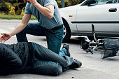 Car driver making emergency call after collision with a cyclist on the street