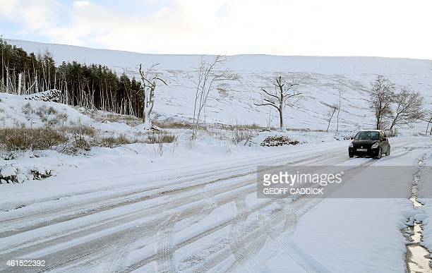 A car drives along a slippery road after heavy snow in Brecon Beacons National Park south Wales on January 14 2015 More than 100 schools and...