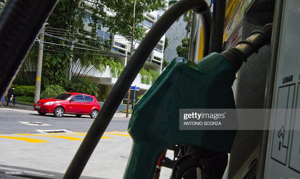 A car drives along a street in front of a petrol station on January 30, 2013 in Rio de Janeiro, Brazil. The price of the fuel in Brazil increased in 6,5% at the refinery, meaning 4,6% to the customers at the petrol pump.