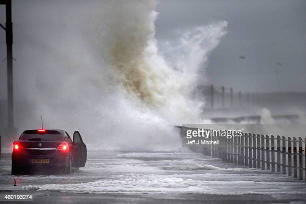 A car drives along Seaview road as waves crash over on December 9 2014 in Saltcoats Scotland The Met Office has issued a yellow weather warning for...