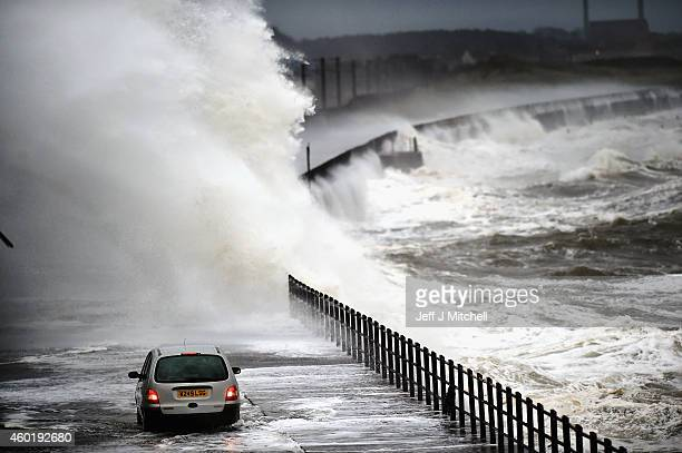 A car drives along Seaview road as waves crash over the promenade on December 9 2014 in Saltcoats Scotland The Met Office has issued a yellow weather...