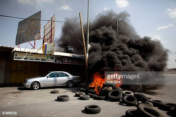 A car drives by burning tyres as Israeli soldiers clash with Palestinians throwing rocks and bottles on October 9 2009 in Qalandyia south of Ramallah...