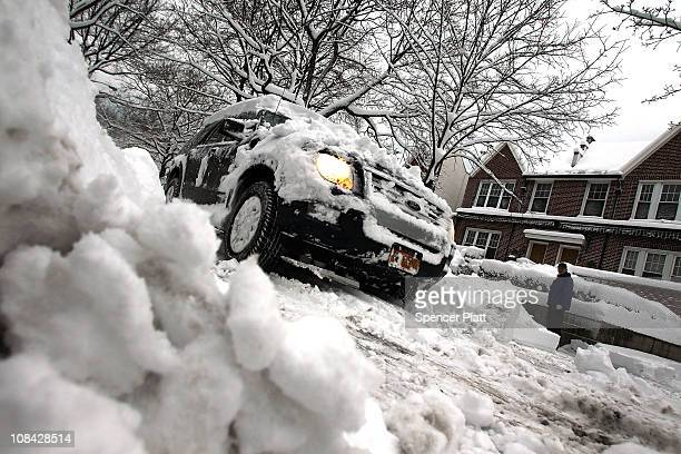 A car drives down a snow covered street January 27 2011 in the Brooklyn borough of New York United States New York City still reeling after the...