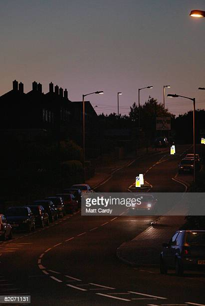 A car drives down a street on the Close Hill estate where police patrol in cars and on foot to uphold a recently introduced voluntary night curfew...