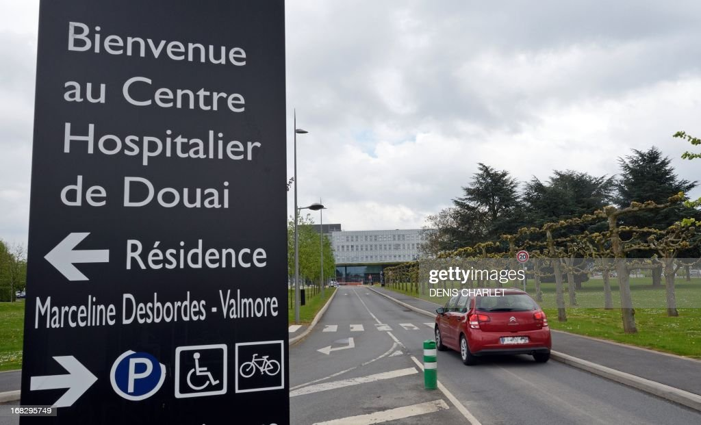 A car drives in front of the hospital where a 65-year-old man who came back to France from a trip to Dubai was diagnosed with the deadly novel coronavirus and is in intensive care in the northern city of Douai, on May 8, 2013. France's health ministry reported the country's first case of a SARS-like virus that has so far killed 18 people, mostly in Saudi Arabia. The virus, known as nCoV-EMC, is a cousin of Severe Acute Respiratory Syndrome (SARS), which triggered a scare 10 years ago when it erupted in east Asia, leaping to humans from animal hosts and killing some 800 people.