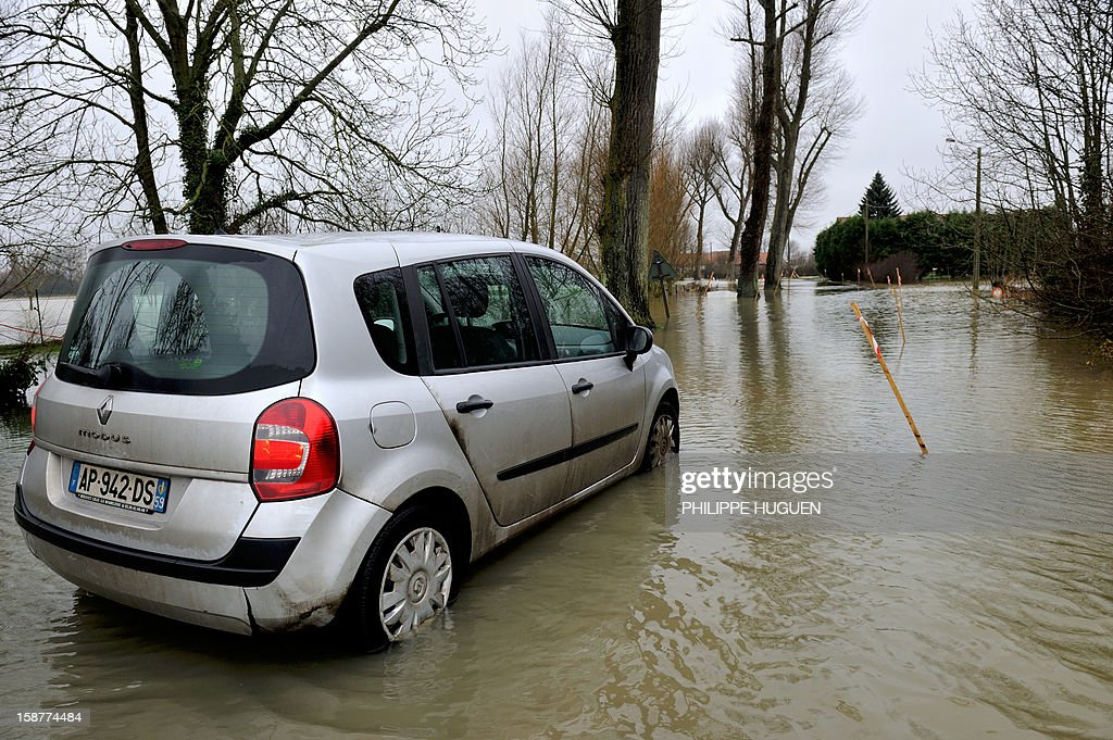 A car drives on a flooded road after the overflowing of the Lys river caused by heavy rainfalls, in Merville, northern France, on December 28, 2012. AFP PHOTO / PHILIPPE HUGUEN