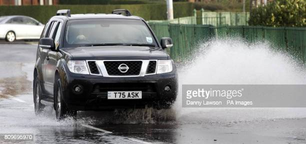 A car drives on a flooded road in Glasgow Scotland as the country braced itself for hurricaneforce winds