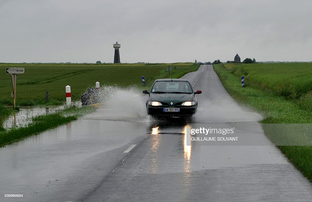 A car drives on a flooded road on May 31, 2016 southern Orleans, following heavy rainfalls which have disrupted the traffic on the A10 highway between Paris and Orleans. The Loiret department is under flood alert and France's weather agency Meteo France maintained today 18 departments under orange alert. SOUVANT