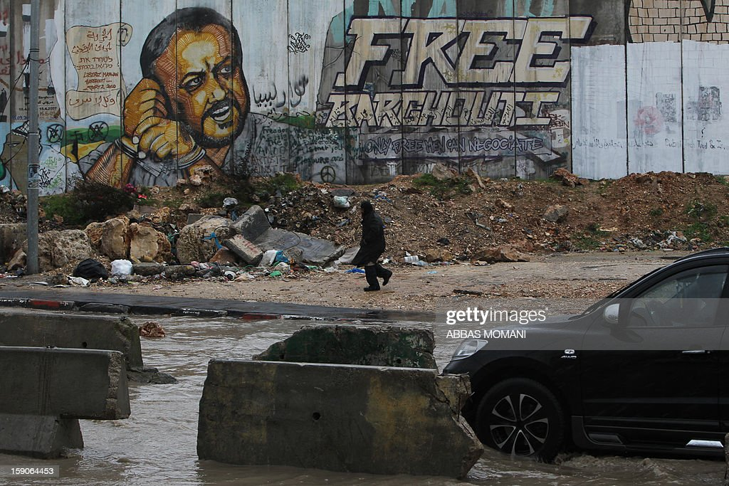 A car drives on a flooded street in front of the Israeli separation barrier at the Qalandia checkpoint in the Israeli occupied West Bank, on January 7, 2013. AFP PHOTO/ABBAS MOMANI