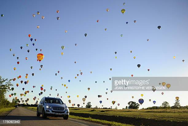 A car drives on a road while hotair balloons fly over ChambleyBussieres eastern France on July 31 to try to set a world record with 408 balloons in...