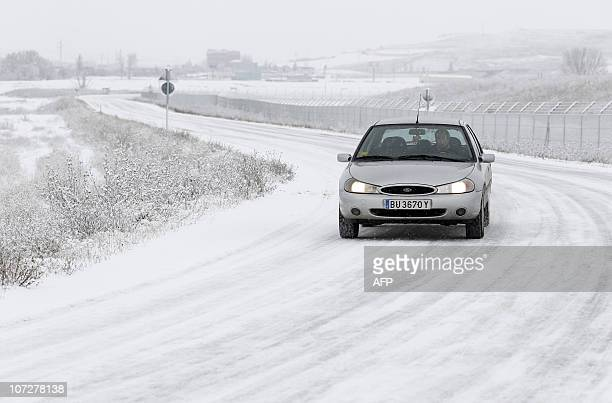 A car drives on a snow covered road as the first snow of the season cloaks the city on December 3 in Burgos Fresh snowfalls swept northern Europe...