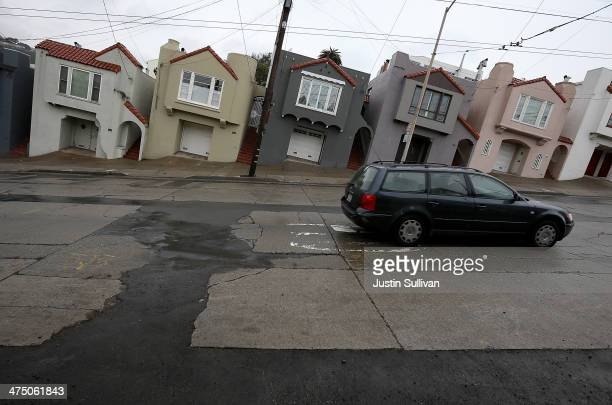 A car drives on a street with cracked asphalt and concrete on February 26 2014 in San Francisco California During a visit to St Paul Minnesota US...