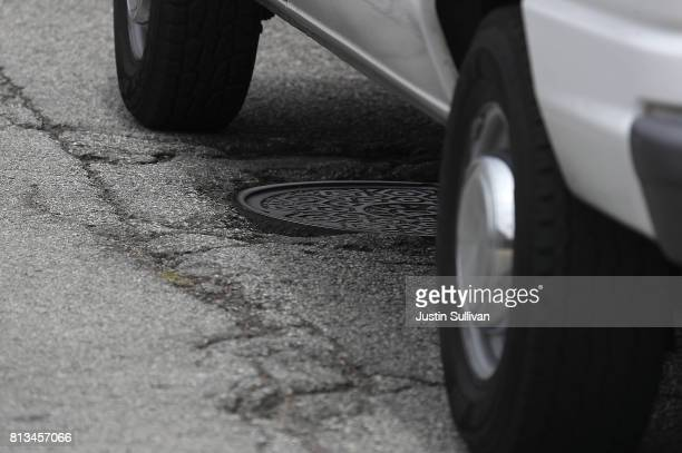 A car drives over a pothole and cracked asphalt on July 12 2017 in San Francisco California According to a report by WalletHub roads in San Francisco...