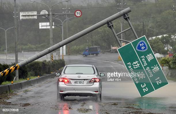 TOPSHOT A car drives pass a collapsed traffic sign toppled by strong winds of typhoon Meranti as it slashes southern Taiwan on September 14 2016...