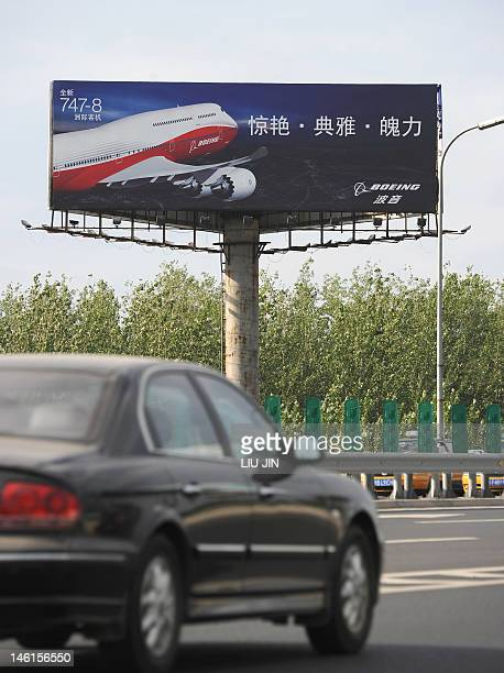 A car drives past a billboard promoting a passenger airplane outside Beijing International Airport on June 11 2012 Airline industry group IATA warned...